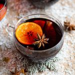 Mulled wine in a glass mug with orange and star anise inside it