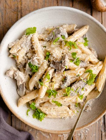 An overhead shot of pasta in a bowl with mushrooms and sausage