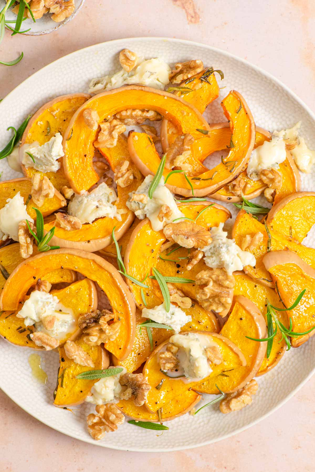 An overhead shot of roasted butternut squash on a serving plate with gorgonzola and walnuts