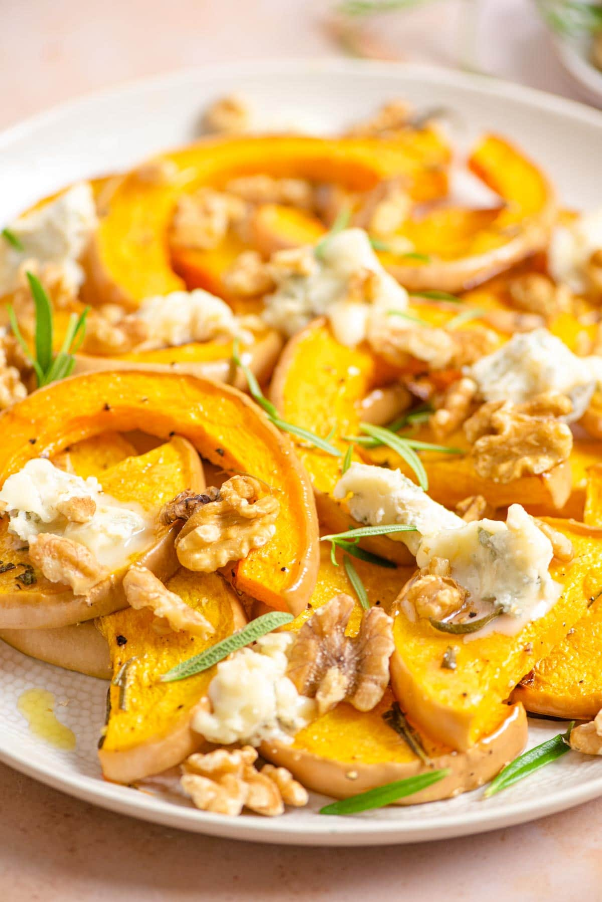 A close up of butternut squash on a serving plate with gorgonzola and walnuts