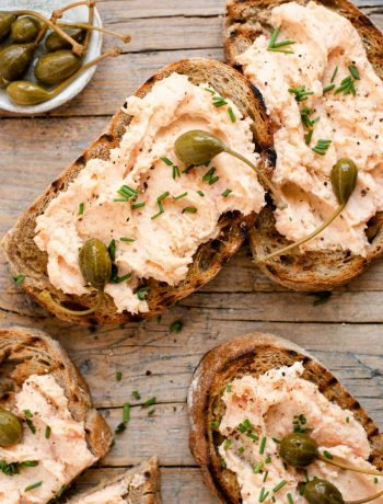 An overhead shot of smoked salmon crostini on a wooden surface