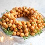 Struffoli honey balls in a ring shape on a cake stand covered in sprinkles