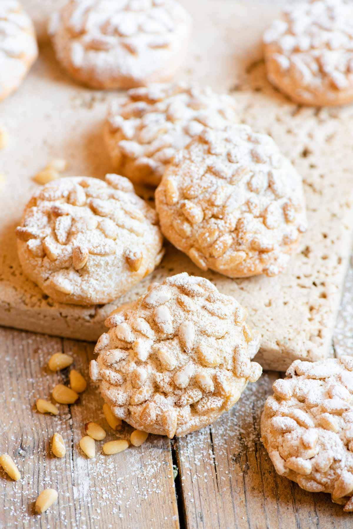 Pignoli cookies on a wooden surface dusted with powdered sugar