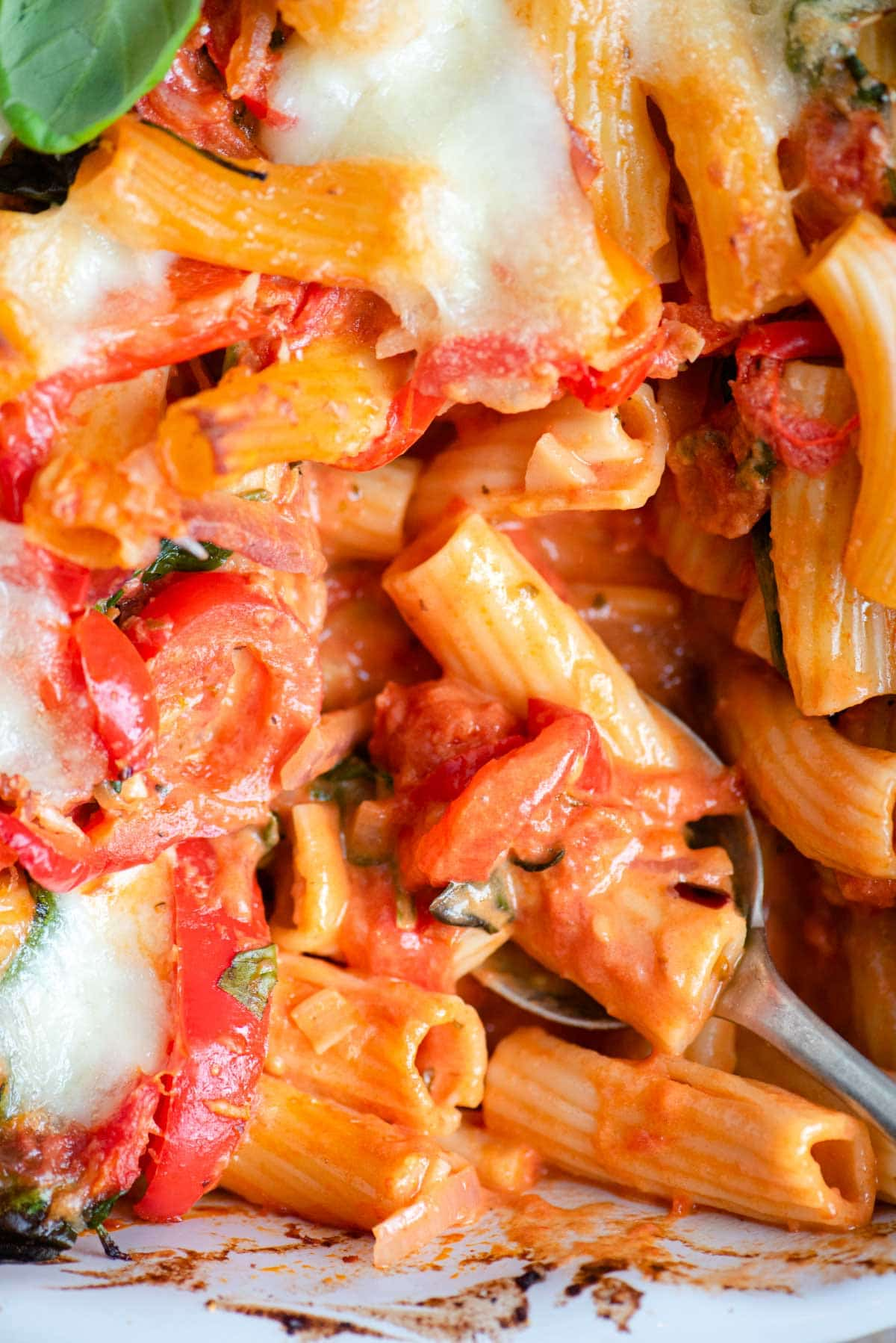 A close up of baked ziti with vegetables in a tomato sauce