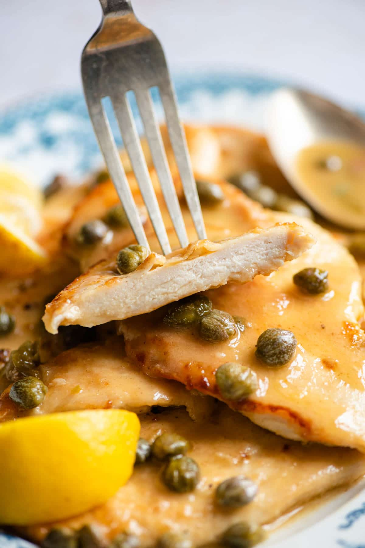 A piece of chicken piccata on a fork