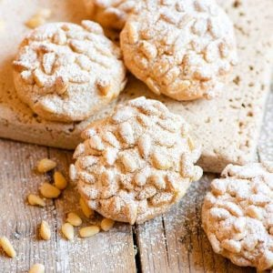 A close up of pine nut cookies dusted with powdered sugar