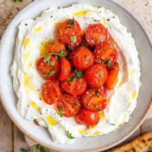 Whipped ricotta in a bowl topped with tomatoes