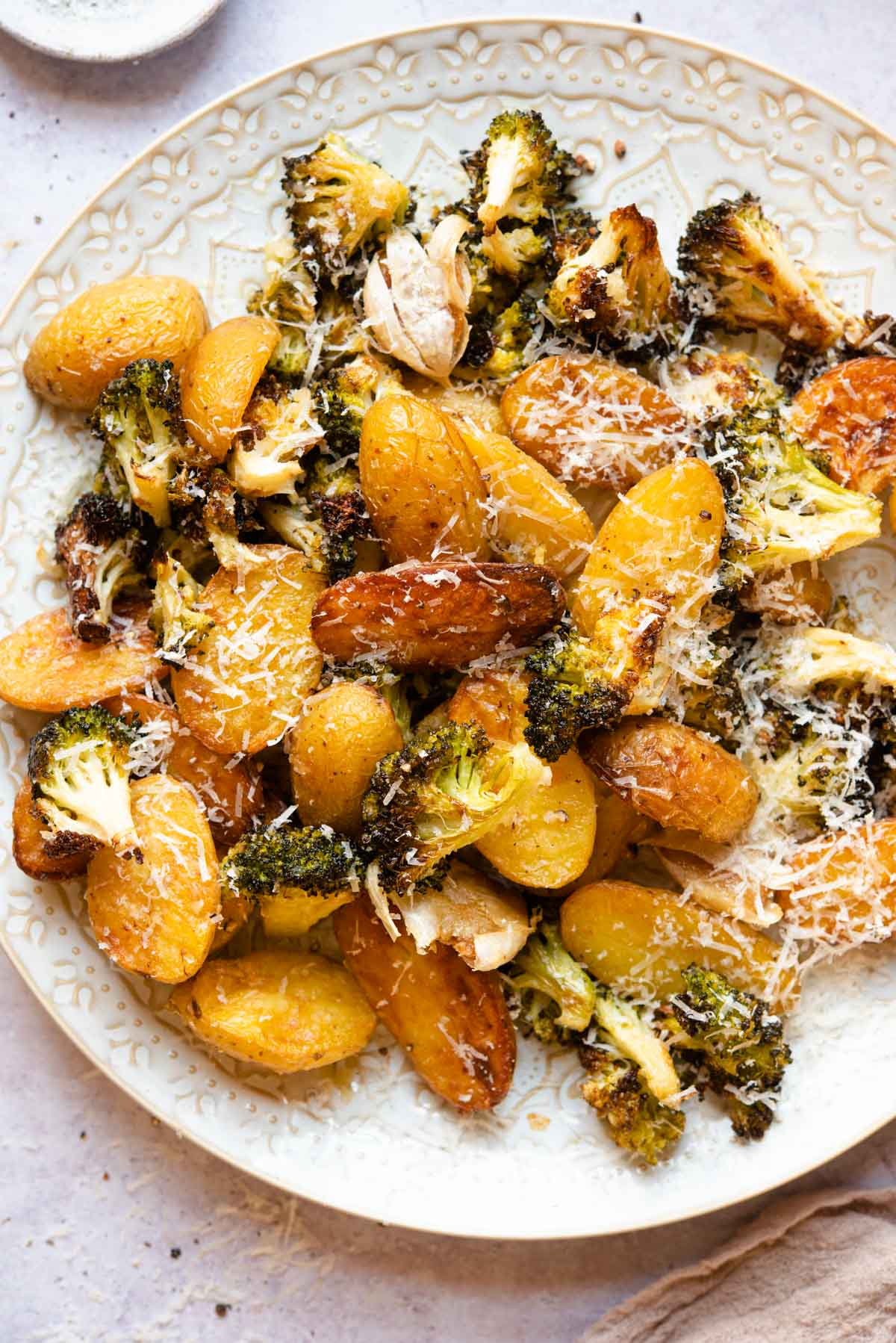 An overhead shot of roasted potatoes and broccoli on a plate