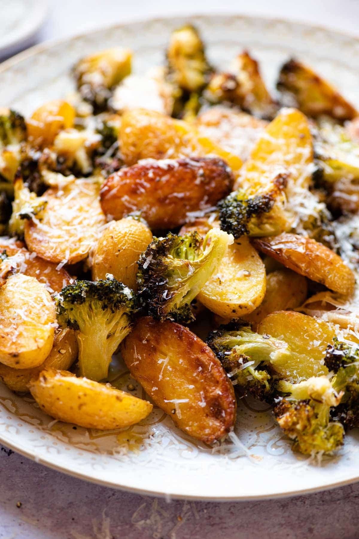A close up of roasted potatoes and broccoli with parmesan
