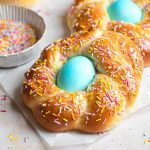 A close up of Italian Easter bread with sprinkles and a blue egg in the middle