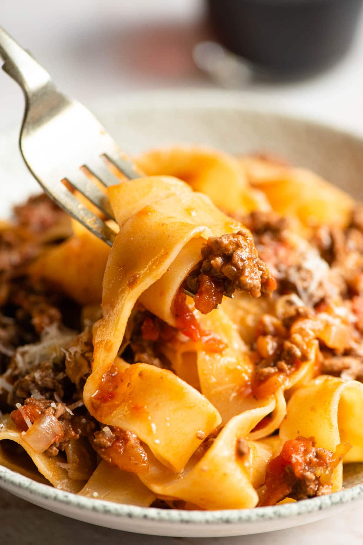 A close up of lamb ragu and pappardelle pasta on a fork