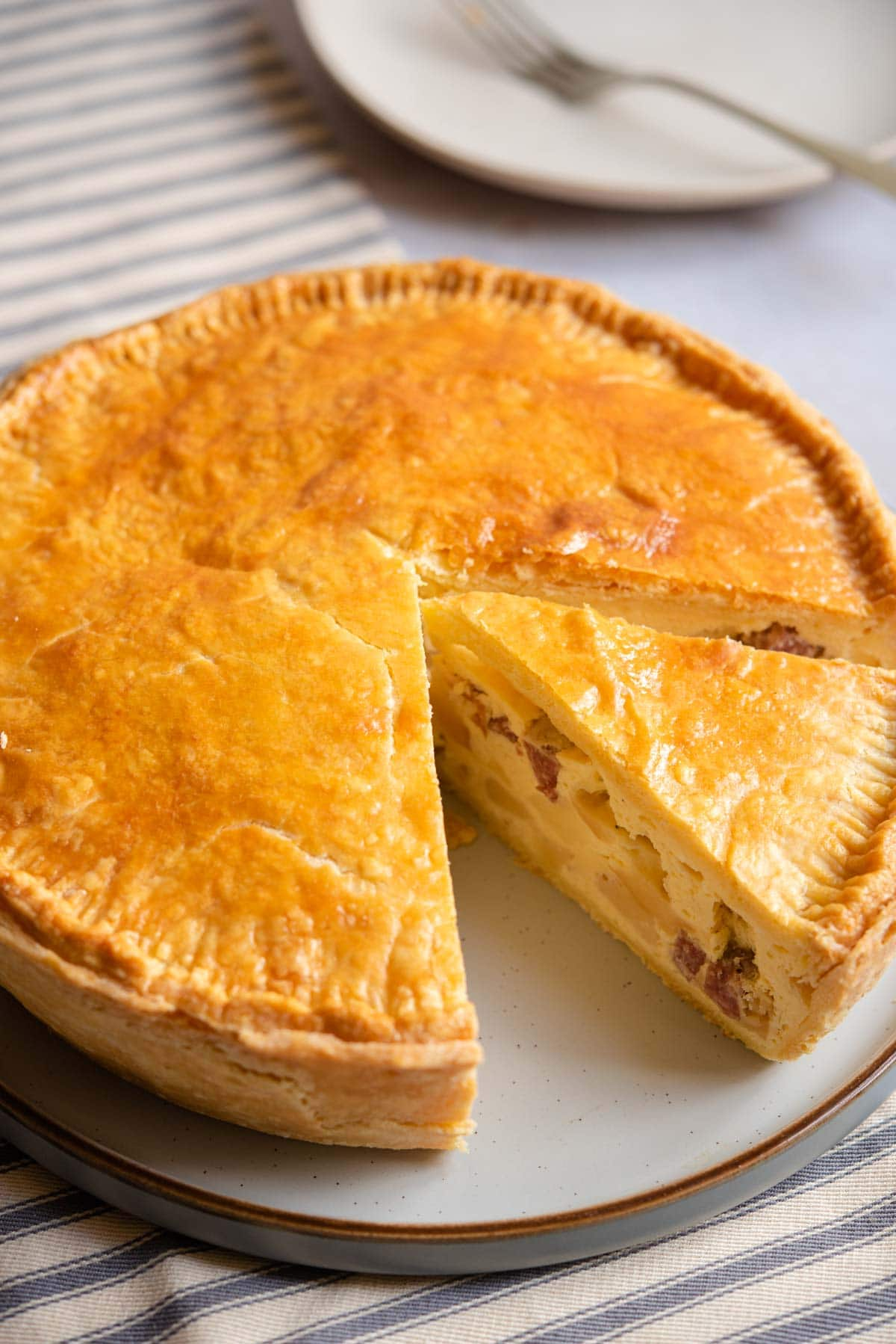 Pizza Rustica on a serving plate with a slice cut