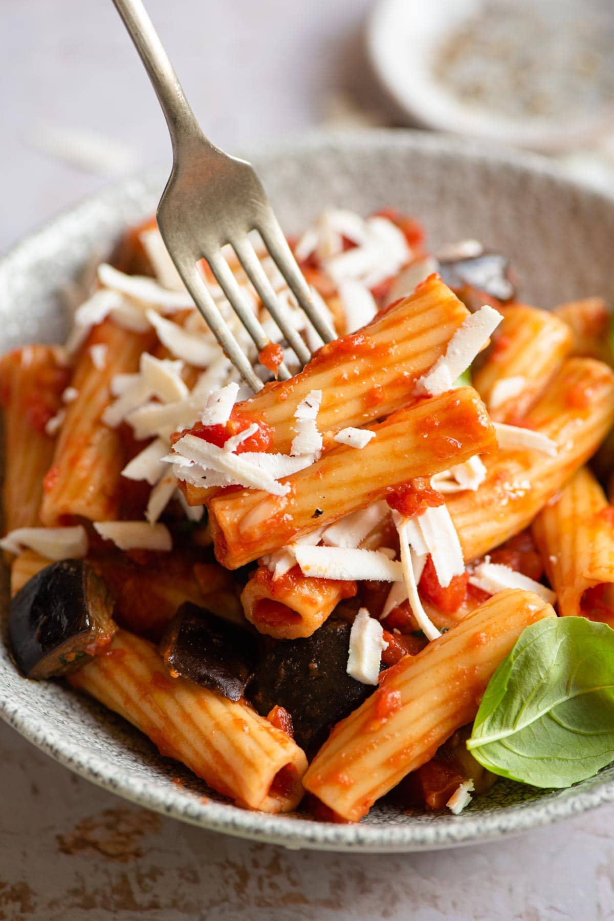 A close up of eggplant pasta on a fork