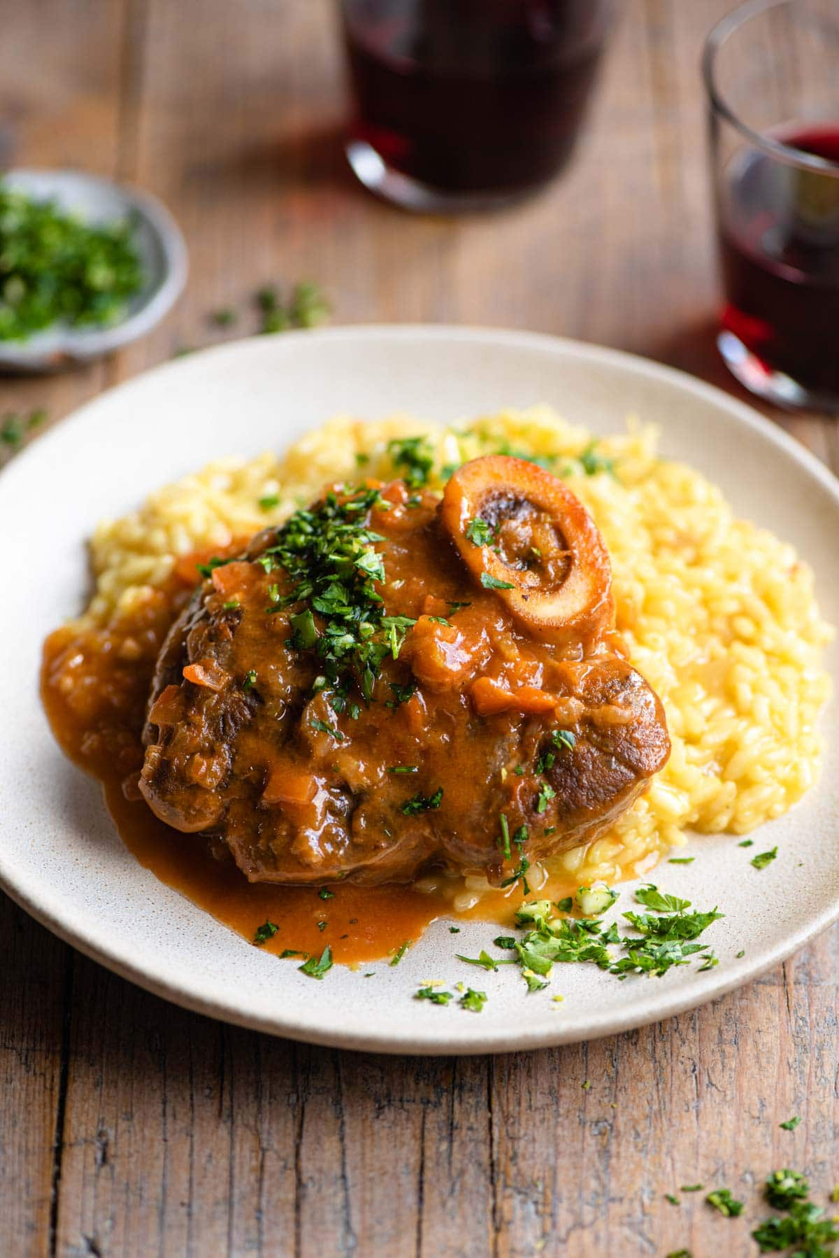 Osso Bucco on a plate of saffron risotto and topped with gremolata