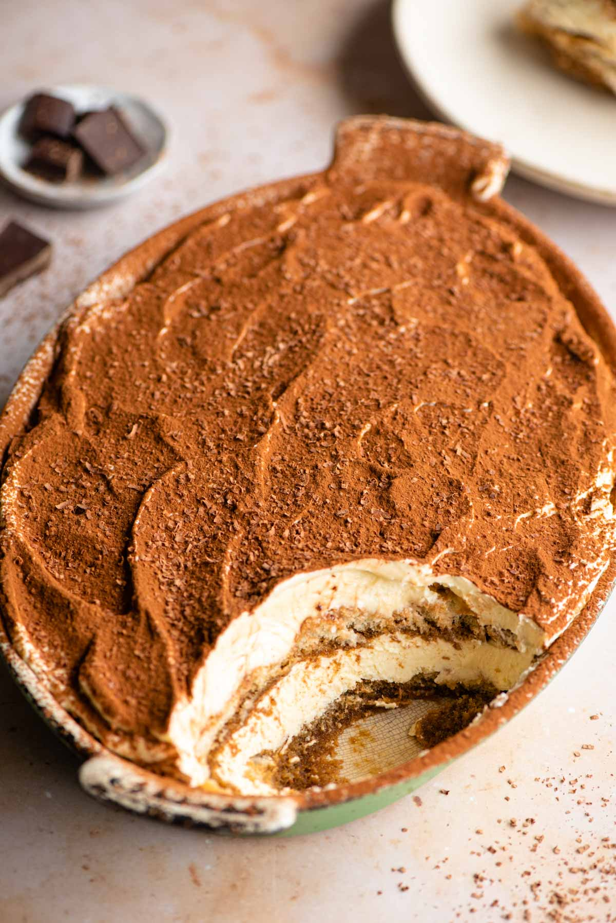 An oval dish of Tiramisu with a scoop out