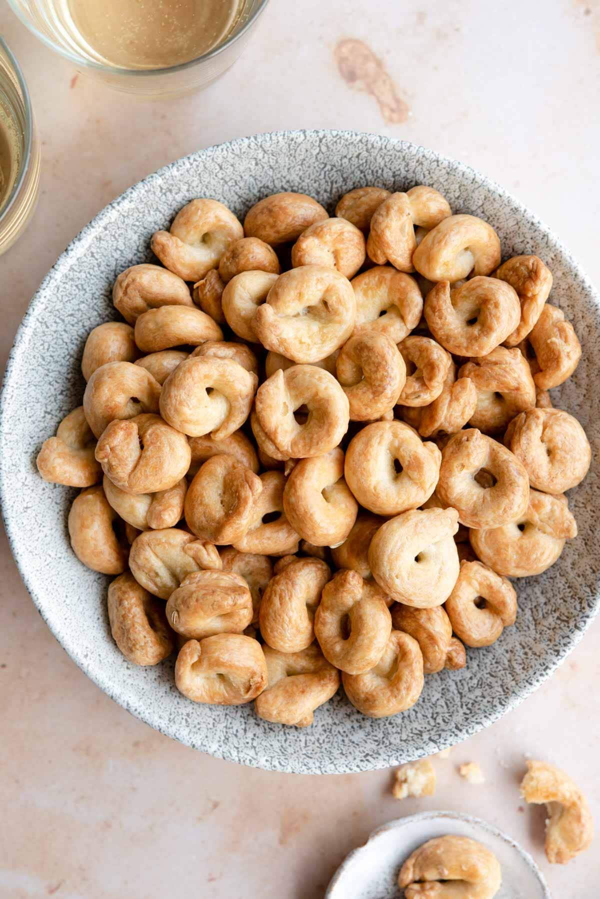 An overhead shot of Taralli in a bowl with glasses of wine at the side