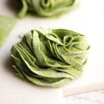 A close up of spinach pasta tagliatelle on a marble cutting board