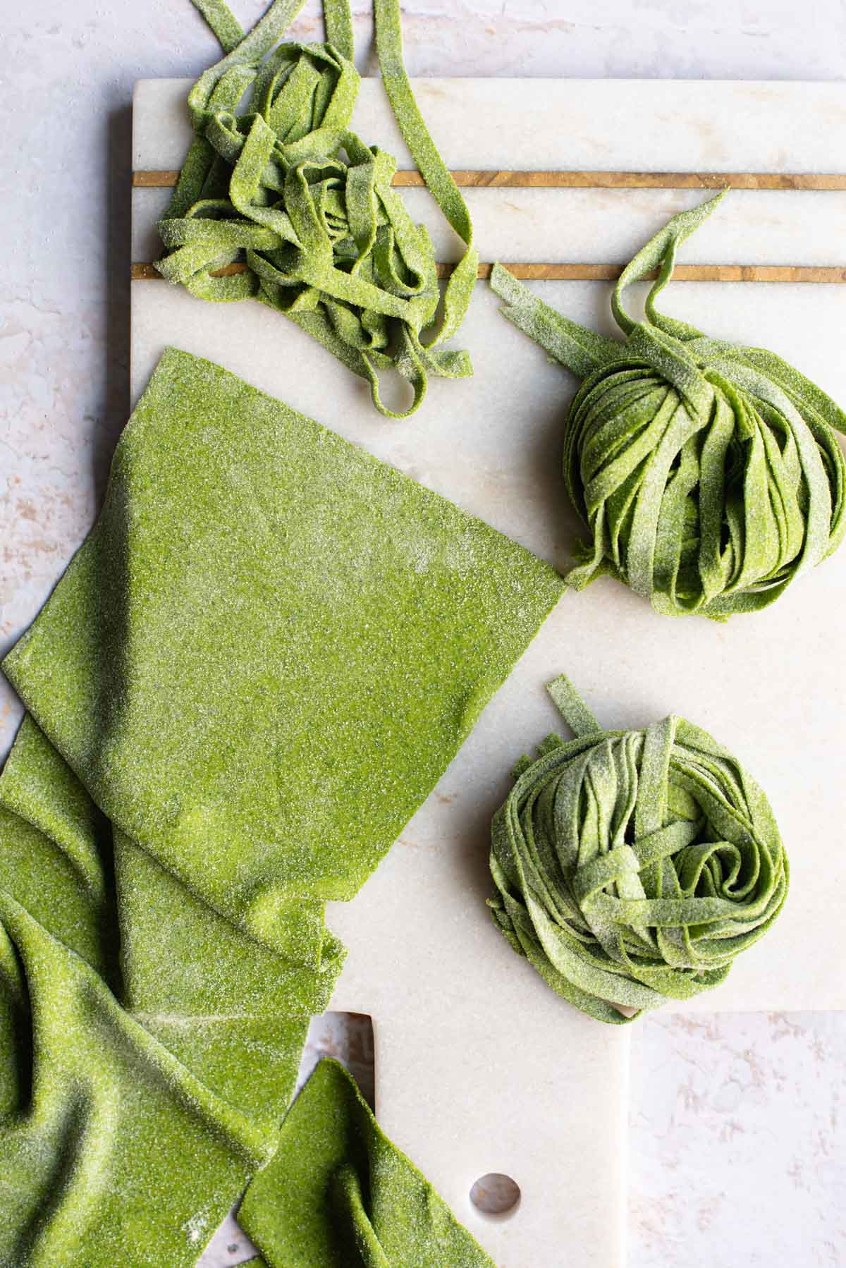 An overhead shot of spinach pasta dough cut into shapes on a light surface