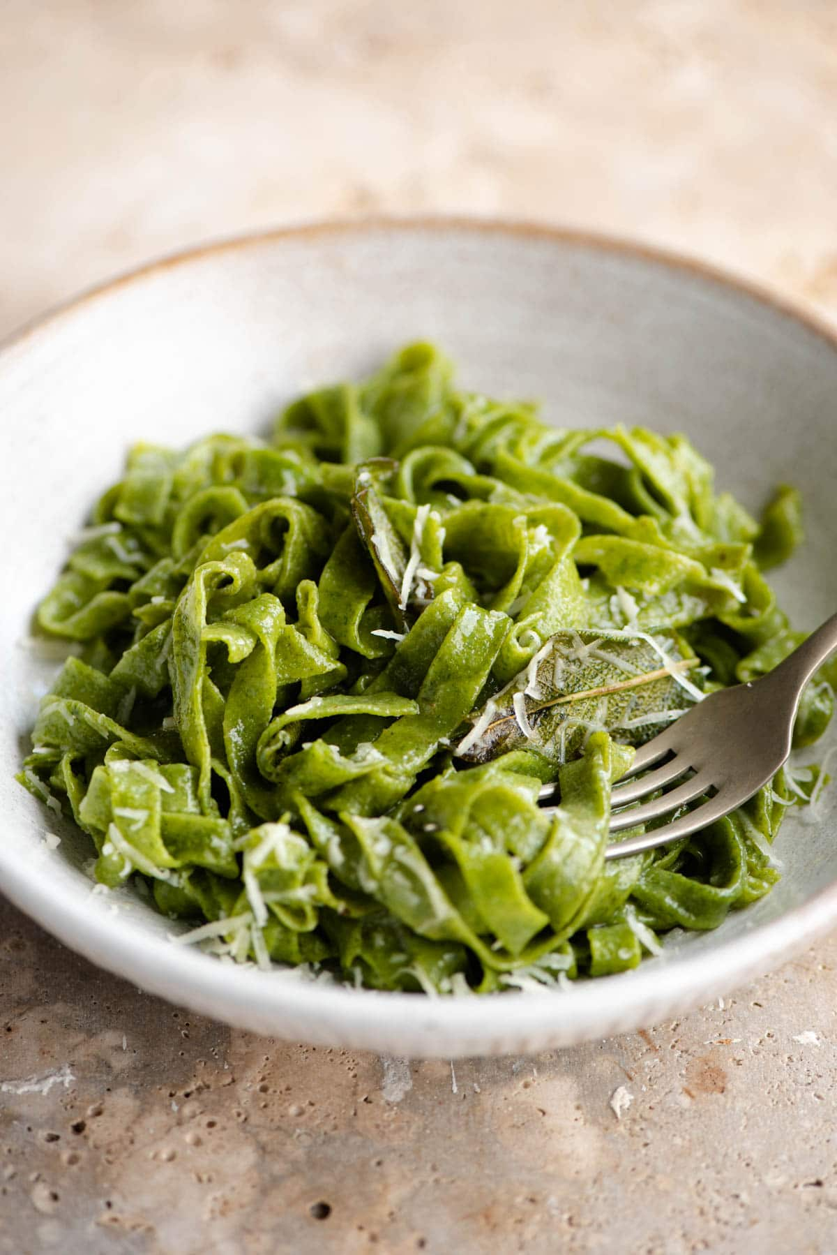 A close up of cooked spinach pasta in a bowl