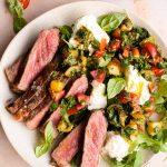 Steak tagliata on a plate with tomato and mozzarella salad