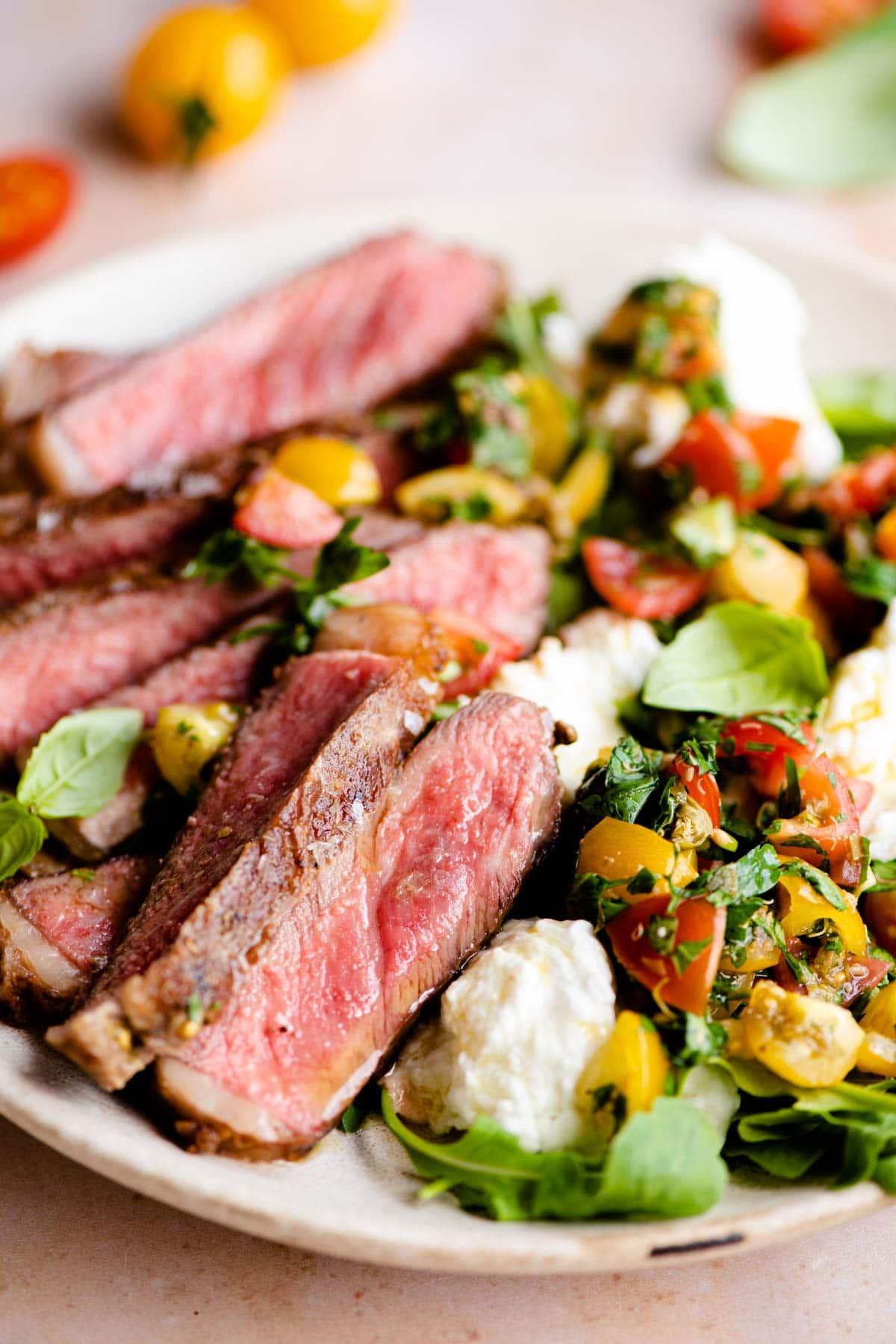 A close up of steak tagliata on a plate with tomato and mozzarella